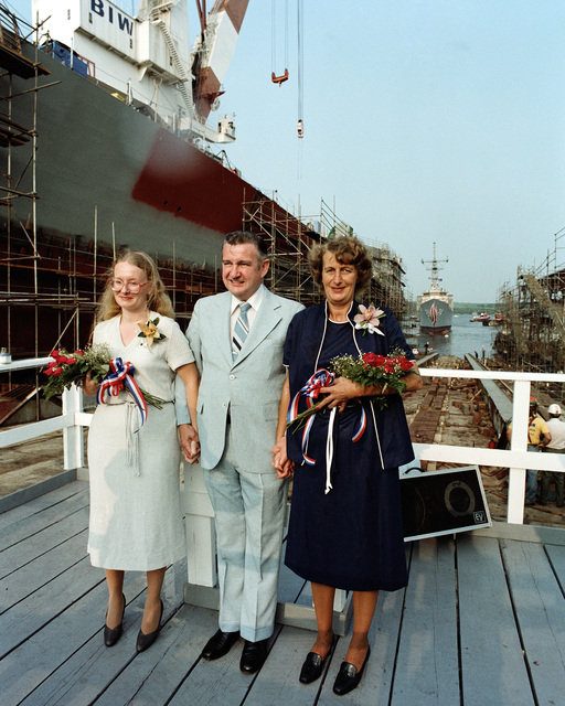 Standing on the speakers platform prior to the launching of the Oliver Hazard Perry class guided missile frigate USS JACK WILLIAMS (FFG 24) are, from left to right, Dana Elaine Carr, sponsor's proxy; John F. Sullivan, president of Bath Iron Works; and Fern Williams Carr, co-sponsor