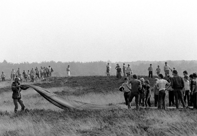 A crowd gathers in a field to watch a paratrooper fold his parachute just after he was airdropped from a U.S. Air Force C-130 during exercise Reforger/Autumn Forge 1980. Autumn Forge is a reserve airdrop taking place here and in Germany and involving mostly U.S. and British troops and equipment
