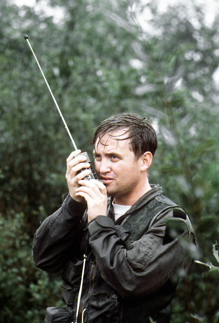 """A """"downed"""" Royal Air Force CPT Roger A. Hamilton contacts a United States Air Force CH-53 Super Jolly helicopter on radio during exercise Reforger '80"""