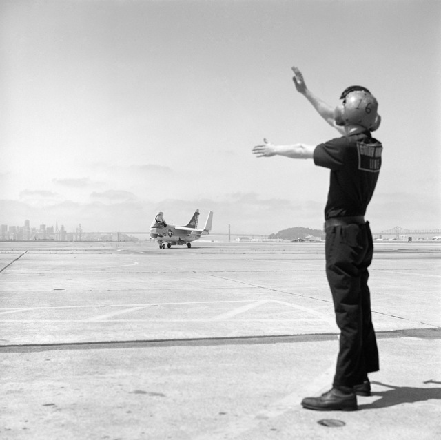 A flight line crewman directs an A-7B Corsair II attack aircraft during activities on the flight line. The Corsair is assigned to Reserve Attack Squadron 303 (VA-303)
