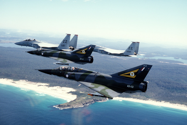 A left side view of four aircraft in-flight during the joint U.S. -Australian Air Force Exercise Pacific Consort. The aircraft are, front to back: an Australian Mirage IIID, and Mirage IIIE, from 77th Squadron Royal Australian Air Force, and two U.S. F-15A Eagles from 67th Tactical Fighter Squadron