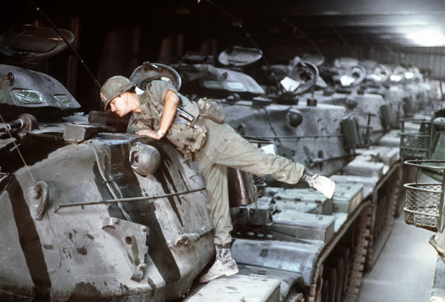 A member of the Army 34th Armor Division readies tanks for the transport from the Maintenance Center and Reserve Storage Activity at Germersheim during exercise Golden Thunder