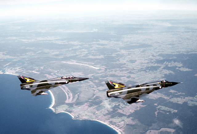 A right side view of two Royal Australian Air Force aircraft. The front aircraft is a Mirage III E and the rear is a Mirage III D. The aircraft are participating in a combined U.S.-Australian Air Force exercise Pacific Consort