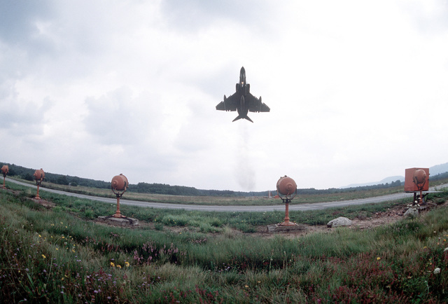 A view of an F-4E Phantom II aircraft taking off past the warning lights along the runway during the exercise Crested Cap