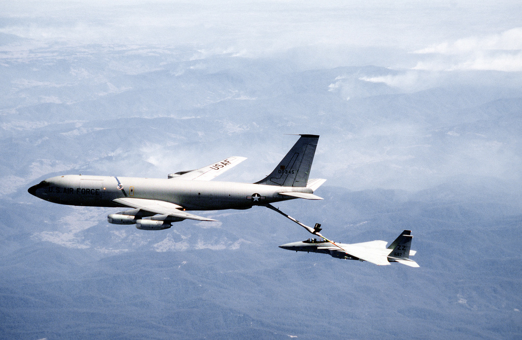 AN air-to-air left side view of a KC-135 Stratotanker aircraft from the 909th Air Refueling Squadron refueling an F-15A Eagle aircraft from the 67th Tactical Fighter Squadron