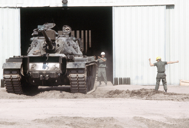 AN Army M-60 tank is being directed out of a warehouse during the exercise Golden Thunder