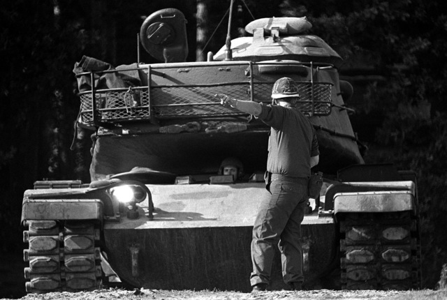 An Army tank commander directs a tank driver during Exercise Reforger '80