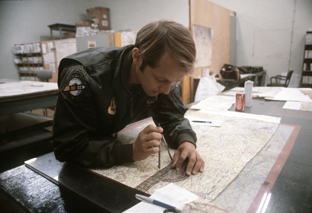 CPT Mark Wright, an F-4E Phantom II pilot of the 336th Tactical Fighter Squadron, charts a map during the exercise Crested Cap