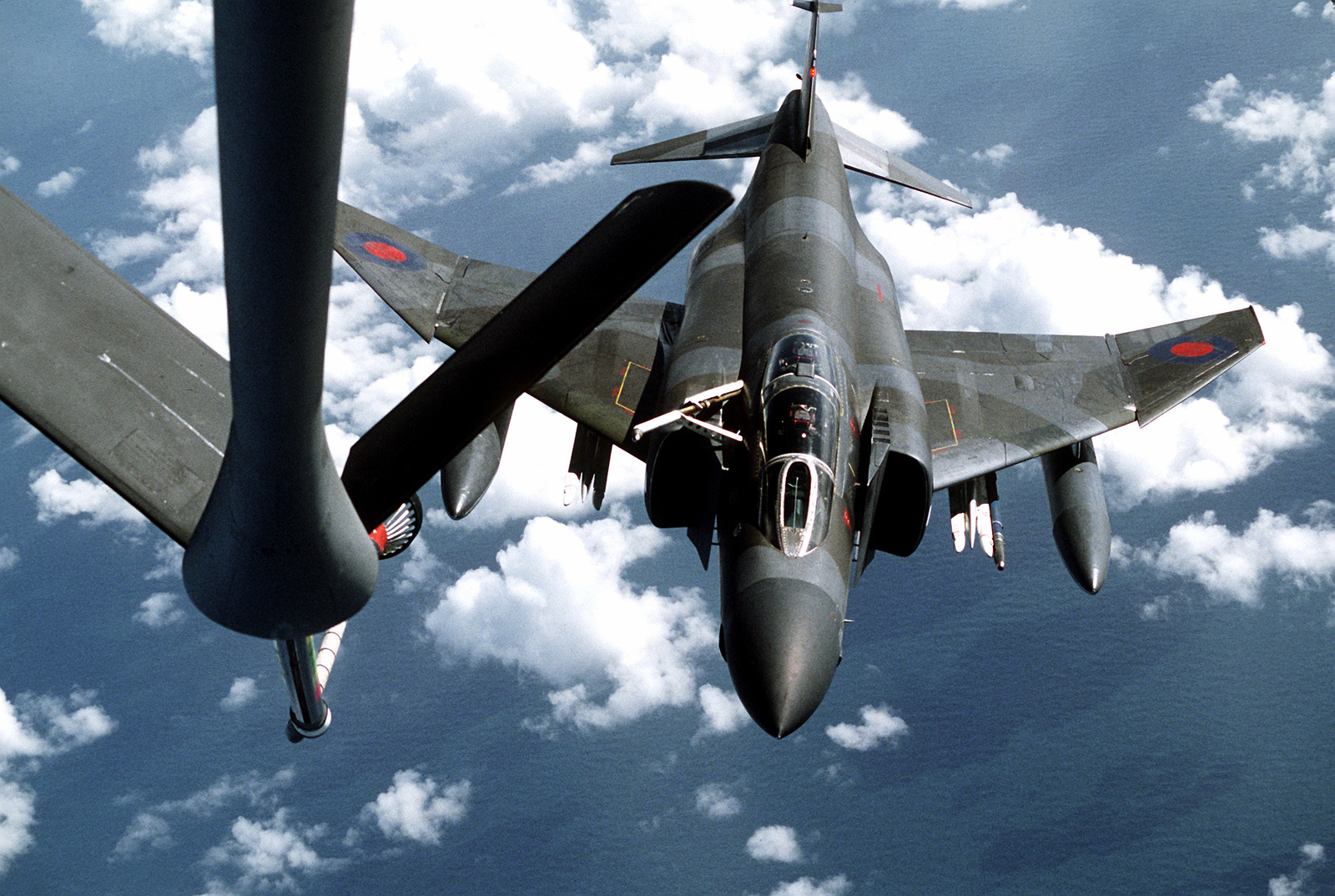 High angle front view of a Royal Air Force RF-4 Phantom II aircraft approaching the refueling drogue of a KC-135 Stratotanker for in-flight refueling. The KC-135 is assigned to the 306th Strategic Refueling Wing