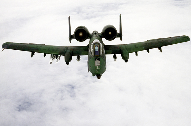 High angle front view of an A-10 Thunderbolt II aircraft, assigned to the 81st Tactical Fighter Wing, in flight. The aircraft is equipped with multiple ejection racks (MER) and is carrying an AGM-65 Maverick missile