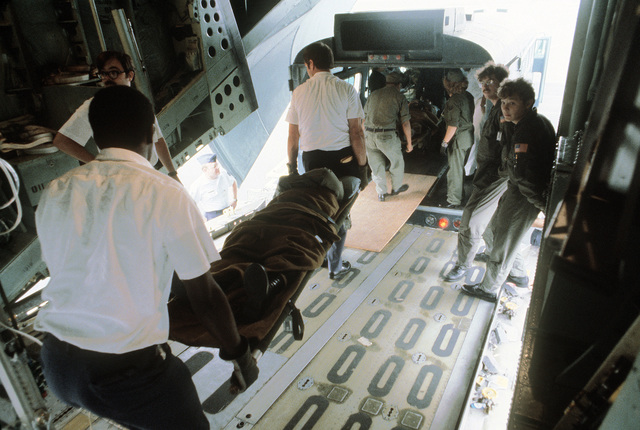 Litter patients are being transferred from a C-141 Starlifter aircraft to a medical bus during exercise Reforger '80