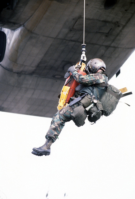 Pararescueman A1C Scott Gearen, on the jungle penetrator, is being lowered from a hovering CH-53 Super Jolly helicopter during exercise Reforger '80