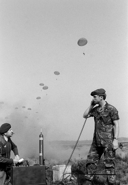 Paratrooper Henry MacNally, tour guide at the military museum here, looks on as U.S. Air Force SSGT Robert Overland, a member of 317th Combat Control Team, uses the communications radio. The two men are participating in exercise Reforger/Autumn Forge 1980, which is a reserve airdrop taking place both here and in Germany and involving mostly U.S. and British troops and equipment