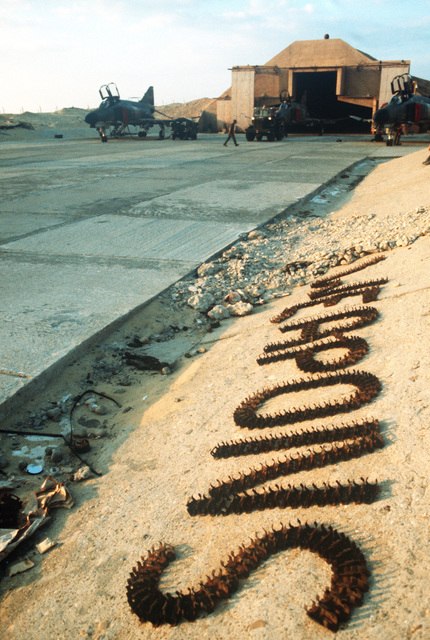 """Rusted bullet clips arranged to spell""""weapons""""in a live ordnance area during Exercise PROUD PHANTOM'80"""