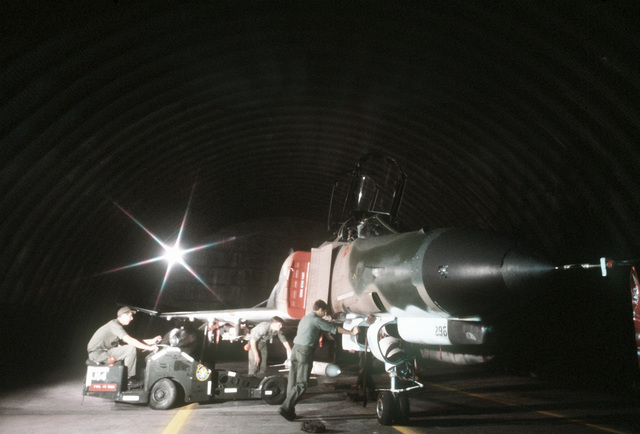 Weapons specialists load a missile on an F-4E Phantom II aircraft with a bomb loader. The airmen are assigned to the 4th Aircraft Generations Squadron participating in the exercise Crested Cap