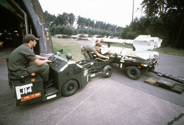 Weapons specialists use a bomb loader to load AIM-9P Sidewinder and AIM-7 Sparrow missiles, from a trailer aboard an F-4E Phantom II aircraft. The airmen are assigned to the 4th Aircraft Generations Squadron participating in the exercise Crested Cap