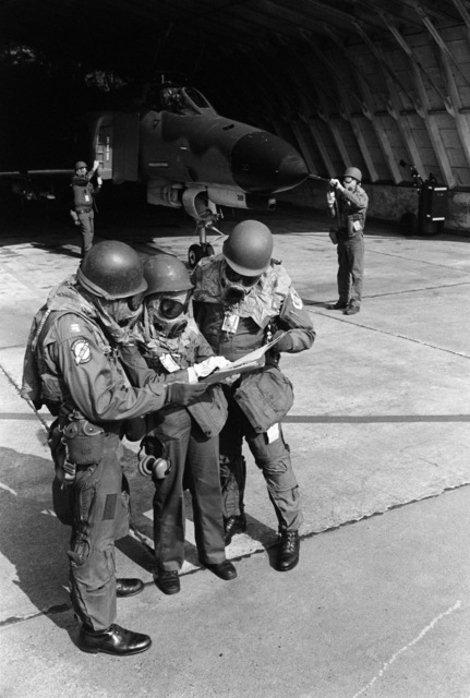 Members of the 4th Tactical Fighter Squadron dressed in nuclear, biological and chemical protective gear check their orders during Exercise CRESTED CAP.  In the background, maintenance personnel place protective covers on an F-4E Phantom II aircraft