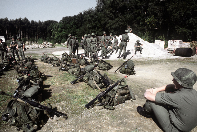 U.S. troops wait to be transported on buses to a mess hall during exercise Reforger '80