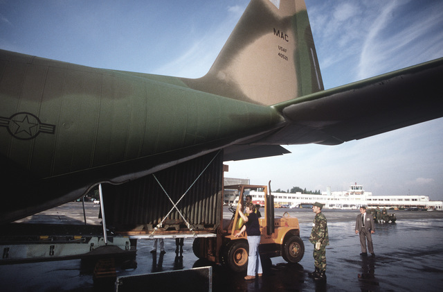 Belgians, using a forklift, help load cargo into a U.S. Air Force C-130 Hercules aircraft during exercise Autumn Forge '80