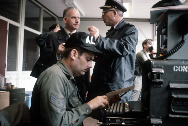 Jay Delleuew, the mayor of Hoogerheide, Holland, and COL Simon Duinker, wing commander, Woensdrecat Air Base, observe teletype operator SSGT Von McKnight during exercise Reforger '80