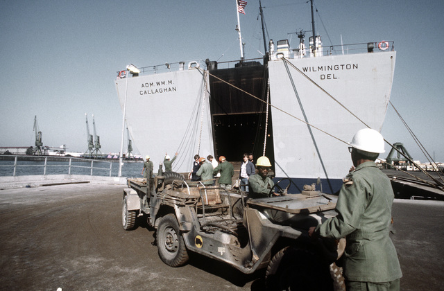 A jeep, towing a trailer, is being unloaded from the GTS ADM WILLIAM M. CALLAGHAN cargo ship during exercise Reforger '80