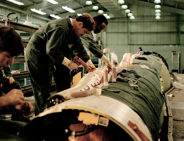 Air Force technicians apply pucky sealant to the raceway on a Minuteman I missile for a modification of the Advance Maneuvering Re-entry Vehicle II