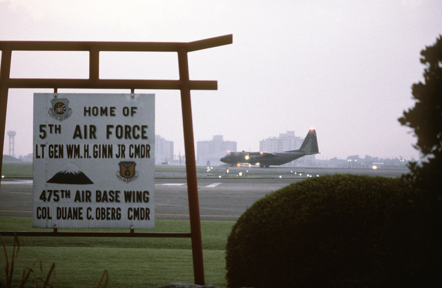 A close-up view of a home sign of the Fifth Air Force and 475th Air Base Wing, as a C-130 Hercules aircraft (in the background) taxis in during exercise Purple Duck, a deployment from Yokota Air Base, Japan, to Kwang Ju Air Base for joint operation readiness maneuvers with Korean troopers