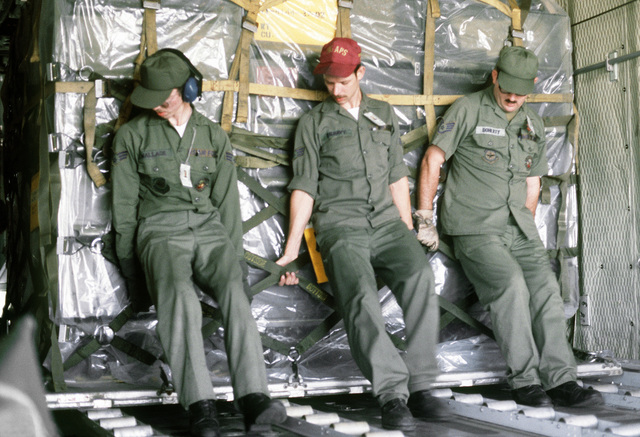 Airmen push a pallet of cargo into a C-130 Hercules aircraft during exercise Purple Duck, a deployment from Yokota Air Base, Japan, to Kwan Ju Air Base for joint operation readiness maneuvers with Korean troopers