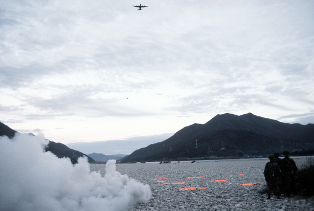 C-130 Hercules aircraft approach a drop zone for airdropping of Korean troopers as combat controllers (in the foreground) signal the aircraft with a flare smoke and marking panels. They are participating in exercise Purple Duck, a deployment from Yokota Air Base, Japan, to Kwang Ju Air Base, Korea, for joint operation readiness maneuvers with Korean troopers