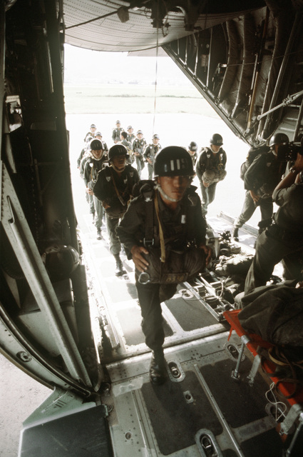 Korean paratroopers board a C-130 Hercules aircraft during exercise Purple Duck, a deployment from Yokota Air Base, Japan, to Kwang Ju Air Base, Korea, for joint operation readiness maneuvers with Korean troopers