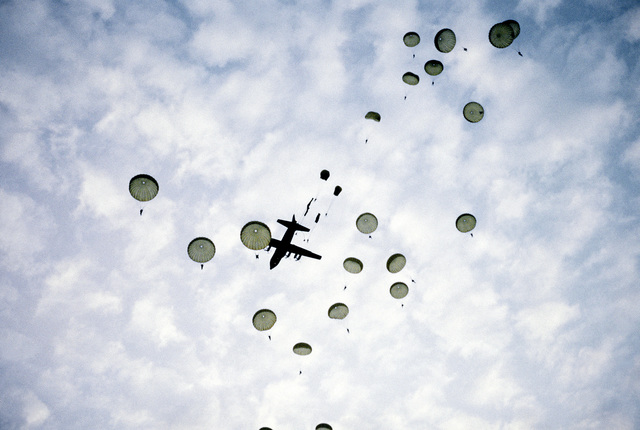 Korean troopers parachute from a C-130 Hercules aircraft over a drop zone during exercise Purple Duck, a deployment from Yokota Air Base, Japan, to Kwang Ju Air Base for joint operation readiness maneuvers with Korean troopers