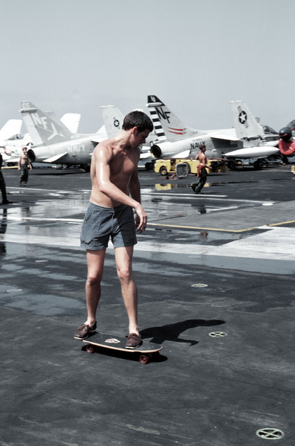 A crewman aboard the aircraft carrier USS MIDWAY (CV 41) skateboards on the flight deck during a stand down period