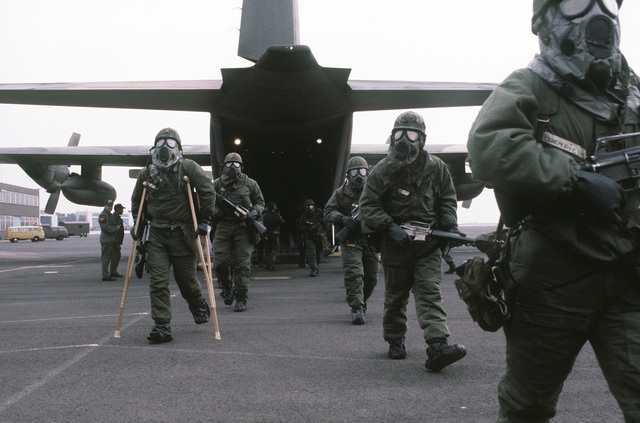 Troops, in chemical warfare gear and carrying M-16A1 rifles, march down the rear ramp of a C-130 Hercules aircraft during exercise Reforger '80