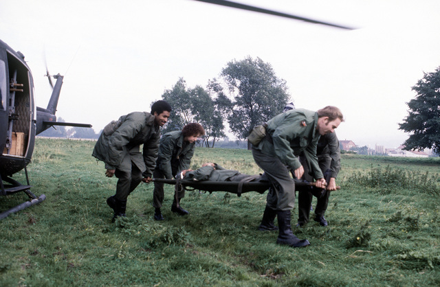 """Medical airmen carry a """"wounded soldier"""" to a UN-1N Iroquois helicopter from the 37th Aeroemedical Evacuation Group during exercise Reforger '80"""