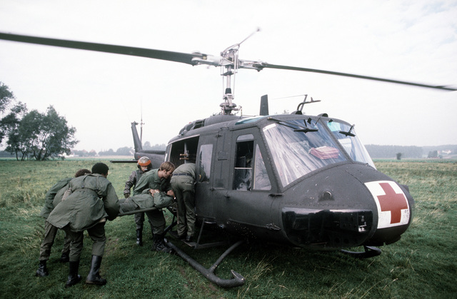"""Medical airmen load a """"wounded soldier"""" aboard a UN-1N Iroquois helicopter from the 37th Aeroemedical Evacuation Group during exercise Reforger '80"""