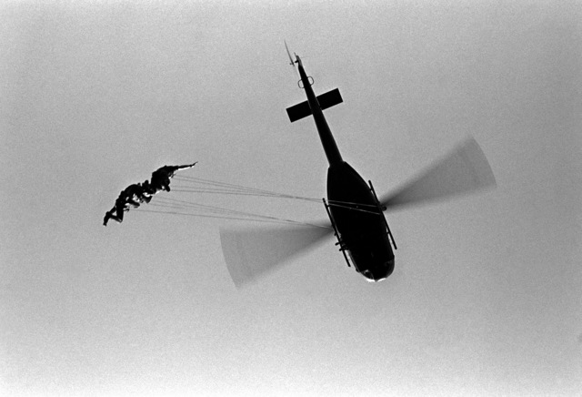 U.S. Army personnel from the 287th Military Police Company and Aviation Detachment, Berlin, rappel from a hovering helicopter during troop recovery training at Tempelhof Central Airport