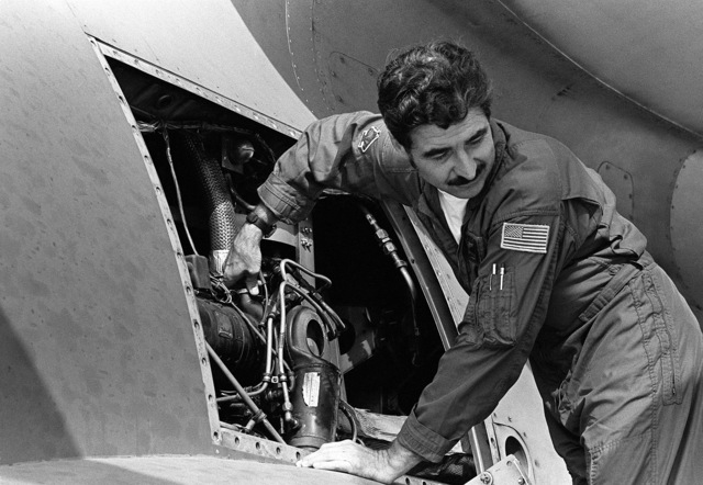 A U.S. Air Force Air National Guard master sergeant checks on aircraft for possible hydraulic leaks while it is on the ground during exercise Reforger/Autumn Forge 1980. Autumn Forge is a reserve airdrop near hear involving mostly U.S. and British troops and equipment