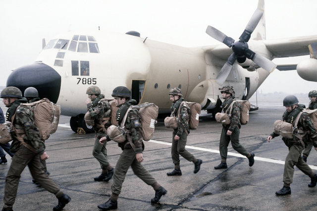 British troops head toward two of three C-130 Hercules aircraft to be loaded for a flight mission with U.S. 82nd Airborne Division troops. The troops will parachute into Arnhem, the Netherlands, to participate in an annual Market Garden (1944 Arnhem Drop) memorial service on Sept. 21