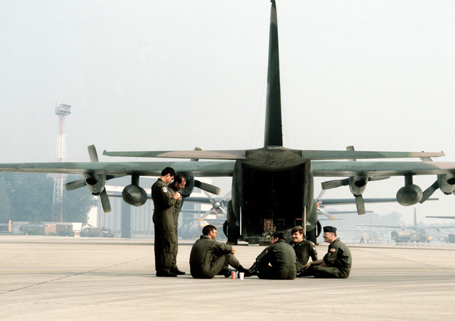 U. S. Air Force Reserve and Air National Guard airmen relax on the airfield next to an aircraft prior to their participation in exercise Reforger/Autumn Forge '80. Autumn Forge will be a reserve airdrop near the base involving mostly U.S. and British troops and equipment