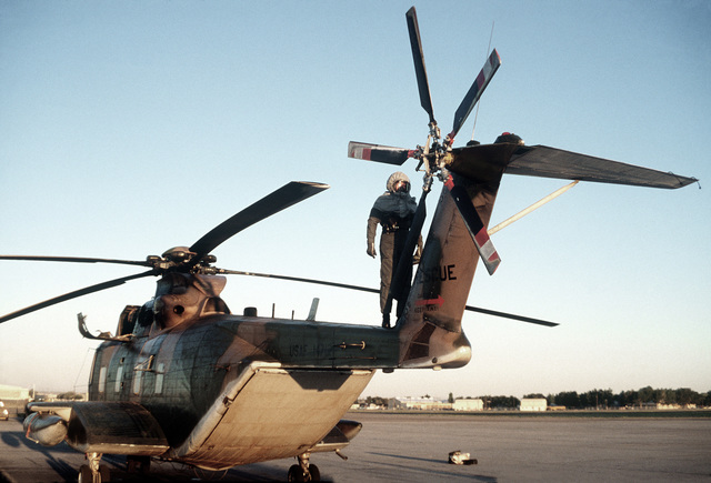 A flight engineer in protective clothing performs a preflight check on an HH-3 Jolly Green Giant helicopter during a chemical warfare training exercise