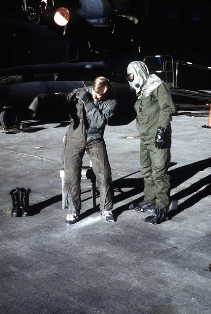A flight engineer puts on protective clothing during a chemical warfare training exercise