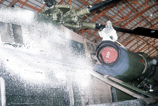 A ground crewman decontaminates an H-53 Sea Stallion helicopter during a chemical warfare training exercise