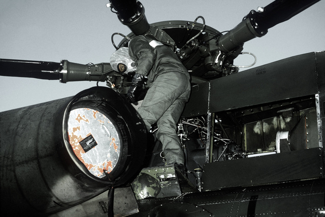 A maintenance crewman in protective clothing performs a preflight check on an HH-3 Jolly Green Giant helicopter during a chemical warfare training exercise