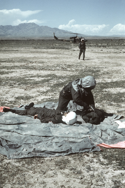 "An airman helps a ""downed pilot"" during a chemical warfare training exercise. A UH-1 Iroquois helicopter is in the background"