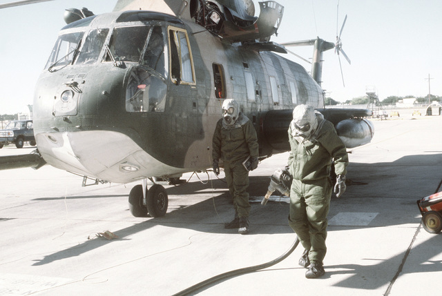Ground crewmen in protective clothing complete refueling of an H-53 Sea Stallion helicopter during a chemical warfare training exercise