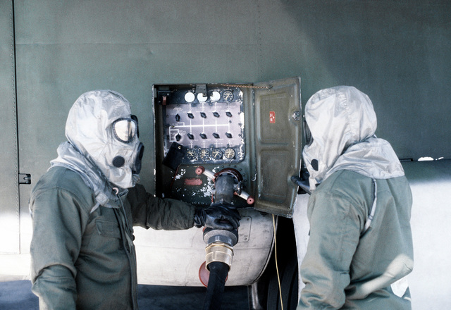 Ground crewmen in protective clothing refuel a C-130 Hercules aircraft during a chemical warfare training exercise
