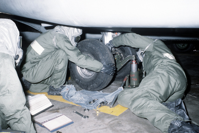 Ground crewmen in protective clothing remove the tire from an H-53 Sea Stallion helicopter during a chemical warfare training exercise