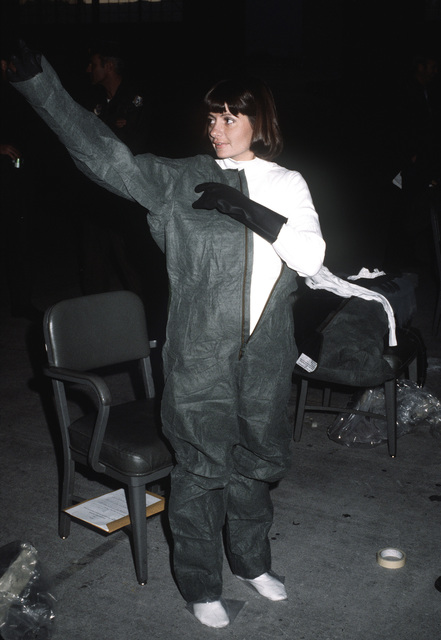 LT. Maureen Duffy, maintenance supervisor, puts on protective clothing during a chemical warfare training exercise