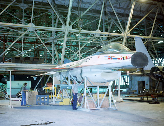 Workmen inspect the fuselage of a YF-16 Eagle aircraft upon its arrival at Hangar #101. The aircraft will be modified for testing as an F-16 at the Rome Air Development Center Newport Site. The effect of various weapons configurations on the aircraft's antennas will be evaluated