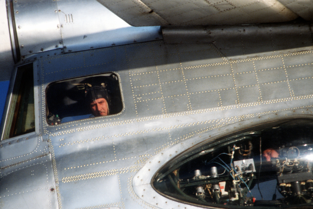 A close-up view of the right side of the tail section of a Soviet Tupolev Tu-95 Bear aircraft showing two crewmen inside. This photo was taken from a U.S. Air Force F-4 Phantom II aircraft observing the Bear over international waters